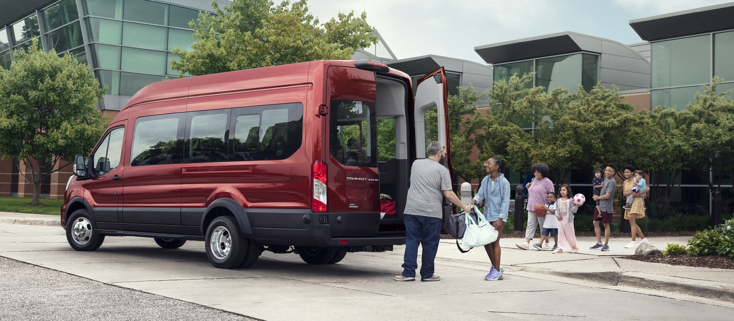 A family walking towards a 2020 Ford Transit Passenger Van while someone helps them load their things into the back