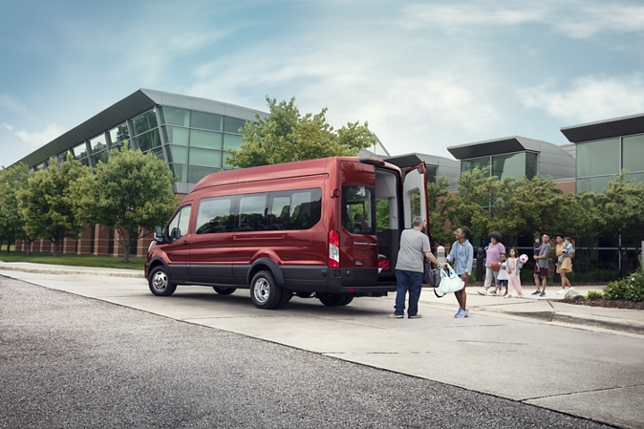 A large family walking towards a 2020 Ford Transit with open cargo doors