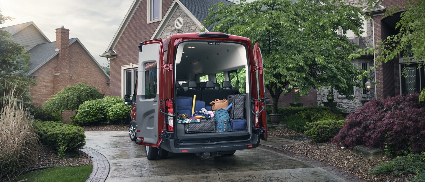 A 2020 Ford Transit parked in front of a house with open cargo doors and luggage in the back