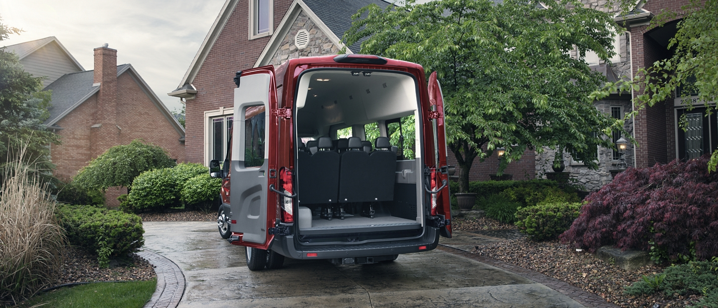 A 2020 Ford Transit parked in front of a house with open cargo doors