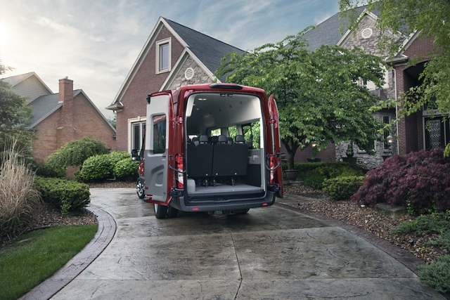 A 2020 Ford Transit with open cargo doors parked in front of a house