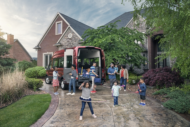 A group of kids playing infront of a 2020 Ford Transit with open cargo doors