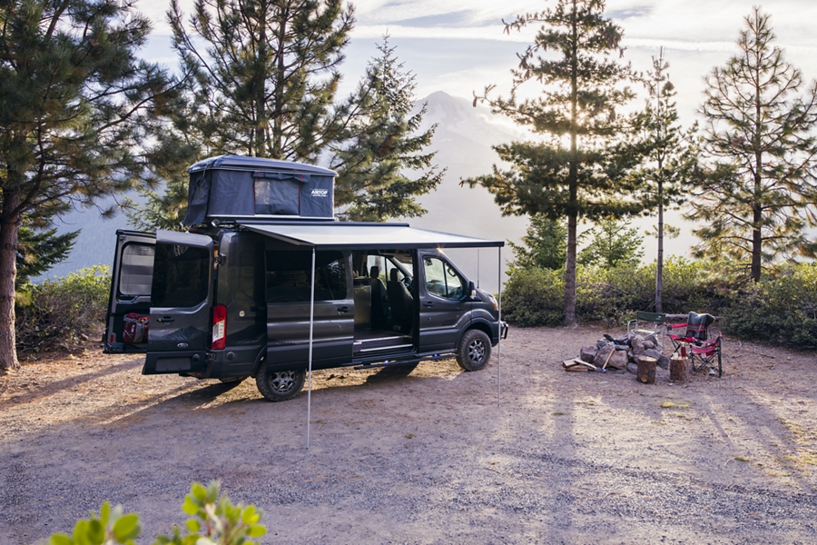 A 2020 Ford Transit passenger van in the wilderness with aftermarket camping accessories