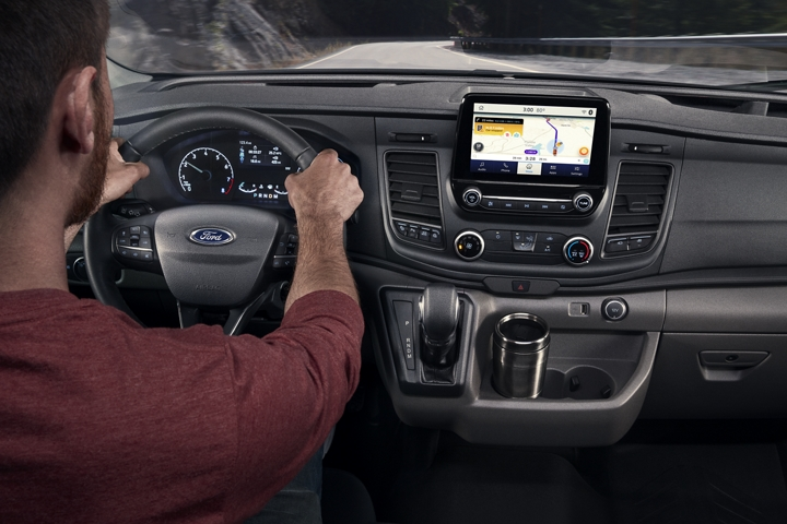 A person behind the wheel of a 2020 Ford Transit using SYNC three