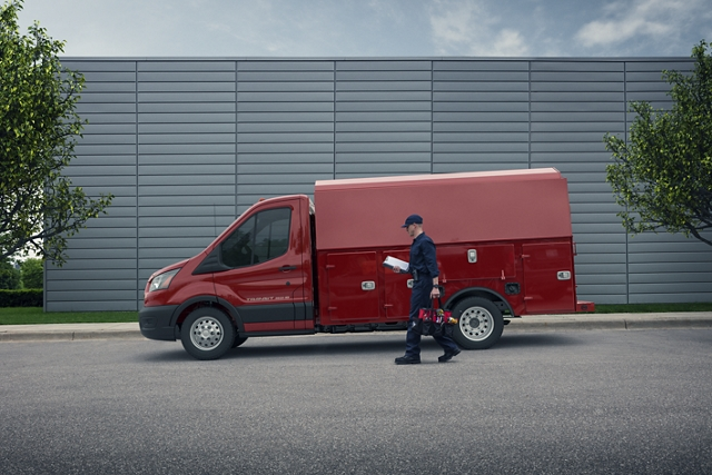 A man approaches a 2020 Ford Transit in Kapoor Red