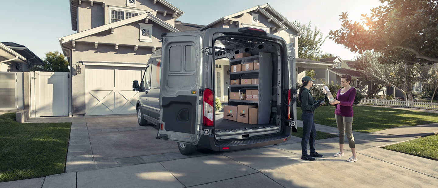 Two people chatting behind a 2020 Ford Transit with the cargo doors open