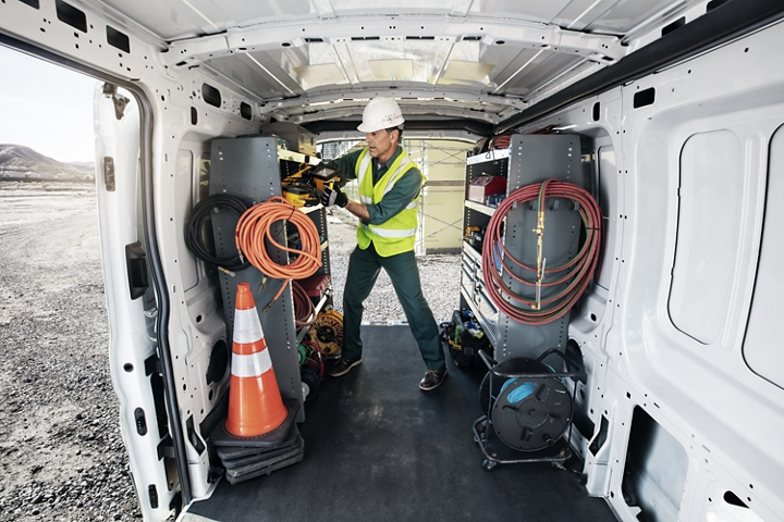 A construction worker in the back of a 2020 Ford Transit