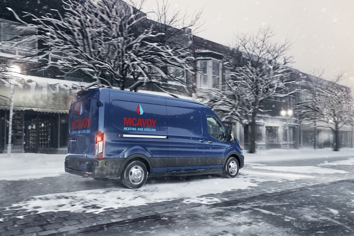 Three quarter rear profile view of a 2020 Ford Transit Cargo Van being driven along a snowy city road