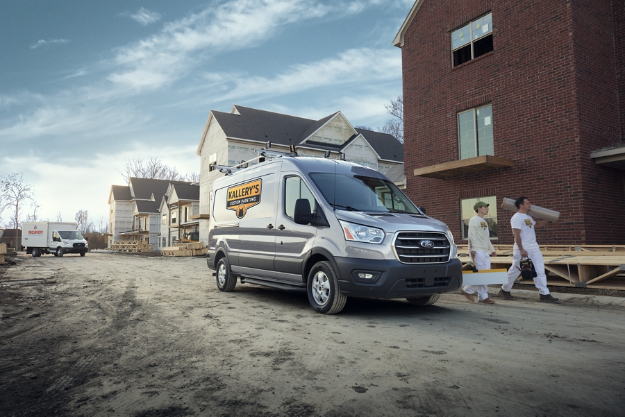 Two workers walk away from the 2020 Ford Transit in Iconic Silver at a construction site