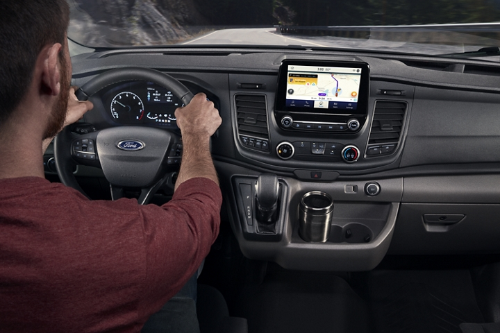 A man behind the wheel of a 2020 Ford Transit using the navigation system on the media hub screen