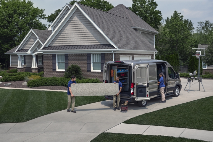 A work crew unloading a 2020 Ford Transit near a suburban home