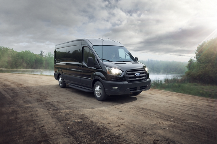 A 2020 Ford Transit in Agate Black being driven on a dirt road