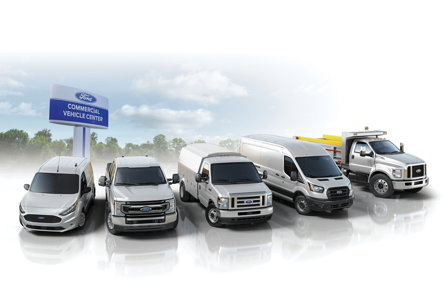 A row of commercial vehicles with a Ford Commercial Vehicle Center billboard in the background