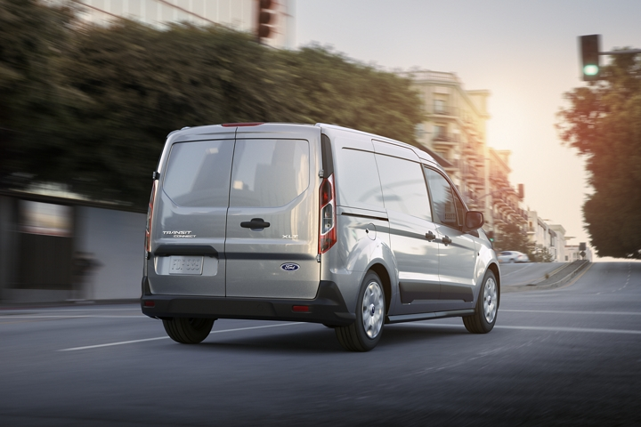 Available swing out rear doors are closed on 2020 Ford Transit Connect Cargo Van being driven down a street