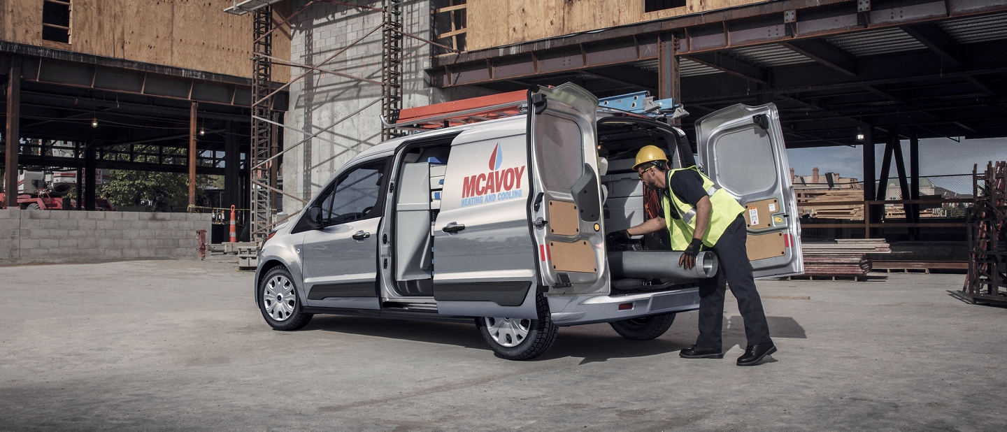 A man working with his 2020 Ford Transit Connect Cargo Vans with doors open