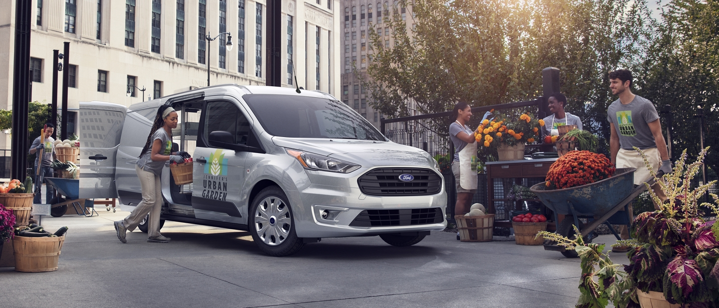 People at a flower market putting the 2020 Ford Transit Connect Cargo Van to work