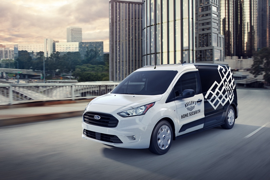 2020 Frozen White Transit Connect Cargo Van with aftermarket business graphics being driven on a city road