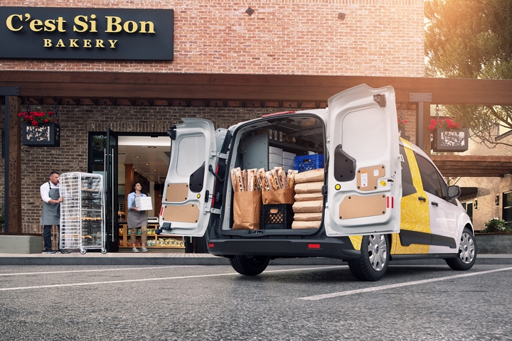 A 2020 Ford Transit Connect Cargo Van with open rear swing out cargo doors is parked in front of a business