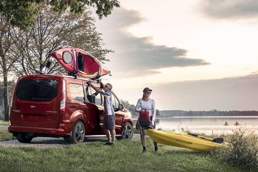 The versatile 2020 Ford Transit Connect Passenger Wagon in Kapoor Red with a man and a woman by a lake during the daytime
