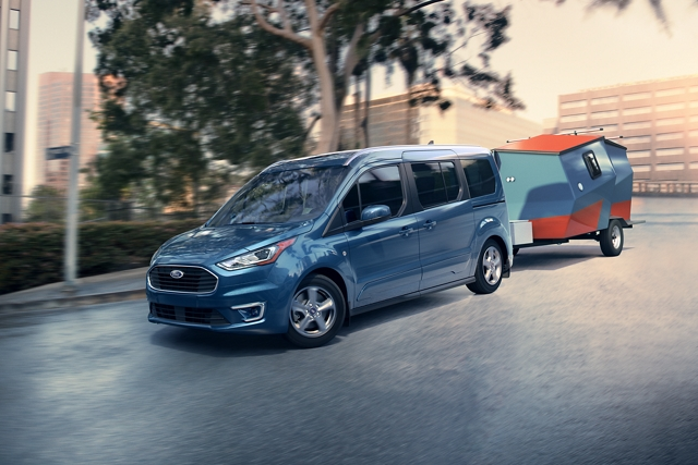 2020 Ford Transit Connect Passenger Wagon in Blue towing a trailer on a city street with no other traffic around