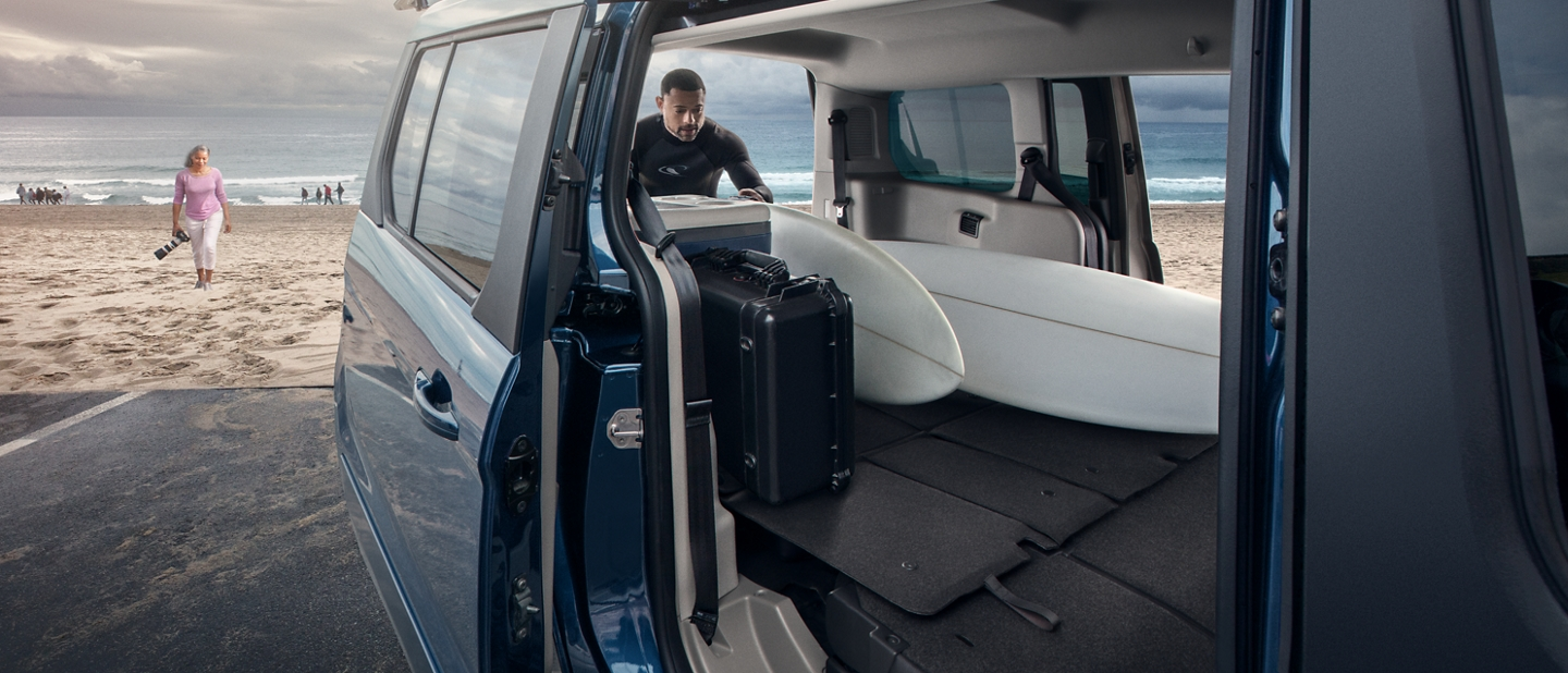 Ample cargo space of Ford Transit Connect Passenger Wagon shown with a man loading