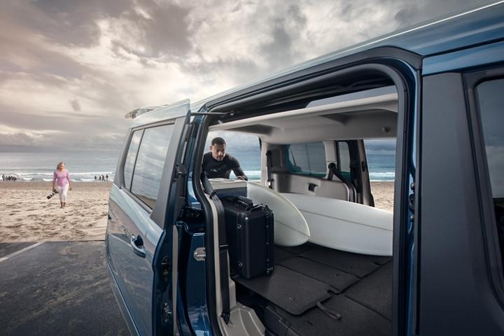 Hombre al lado de una playa cargando un Wagon para PasajerosFord TransitConnect2020 con tablas de surf