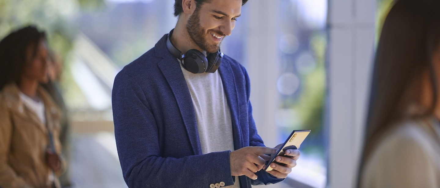 Man wearing headphones uses his smartphone