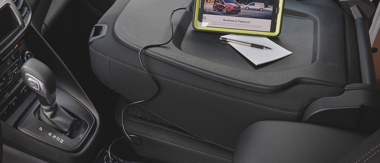 A WiFi tablet rests on the back of a Transit Connects folded passenger seat as it charges using a twelve volt dash socket