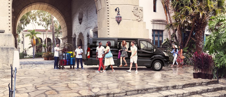 Van para pasajeros transit llevando huéspedes a un centro turístico tropical