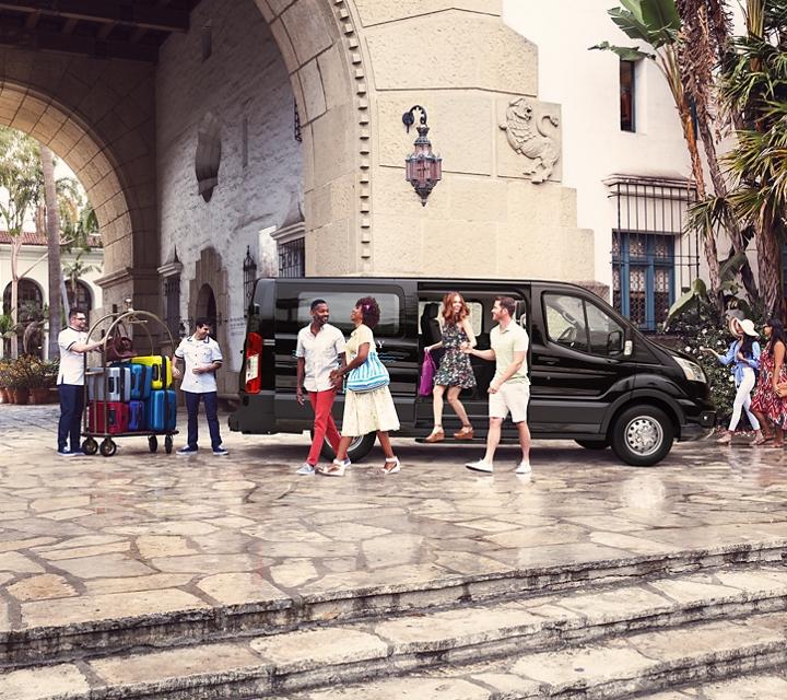 Huéspedes de un centro turístico tropical salen de una van para pasajeros transit