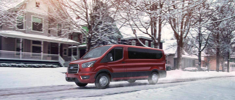 Una van para pasajeros transit pasando por una calle de barrio nevada