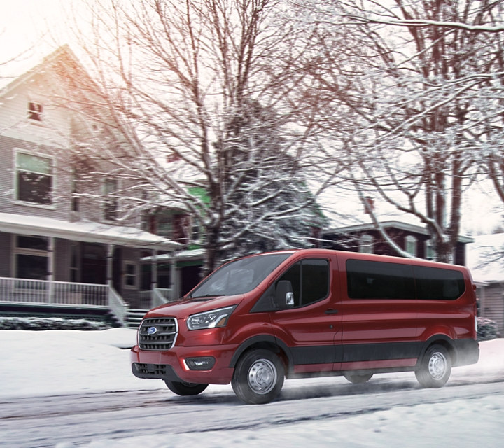 Ford transit passenger van driving on a snowy neighborhood road