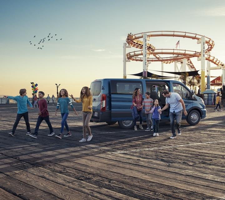 Una familia grande llega a un parque de diversiones en una van para pasajeros transit