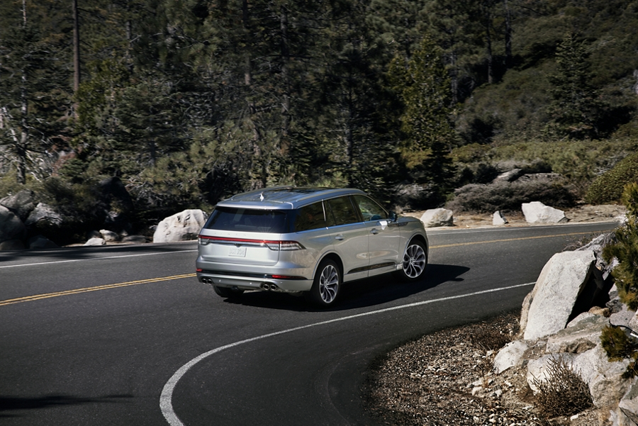 A Lincoln Aviator is shown being driven through a sharp turn on a mountain road
