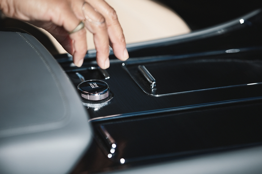 A persons hand is shown reaching for the drive modes knob in the center console