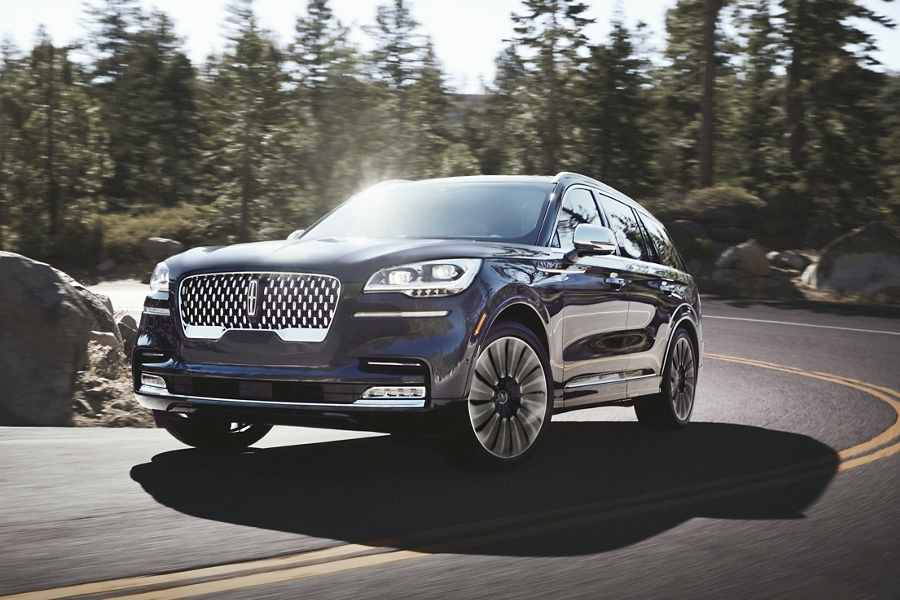 A Lincoln Aviator Black Label is shown being driven through a tight and steep mountainous curve