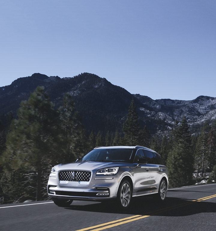 A Lincoln Aviator Grand Touring hybrid model is shown being driven along a winding mountain road