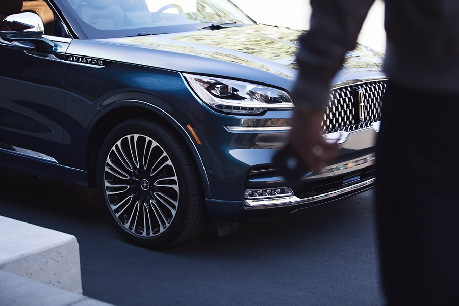 A man is shown approaching a Lincoln Aviator with his phone in his hand which can act as a key to the vehicle