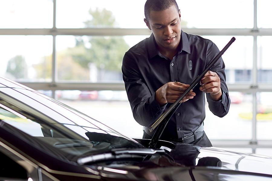 Se muestra un técnico de servicio Lincoln ajustando las escobillas del limpiaparabrisas de un vehículo Lincoln en el área de servicio de un concesionario