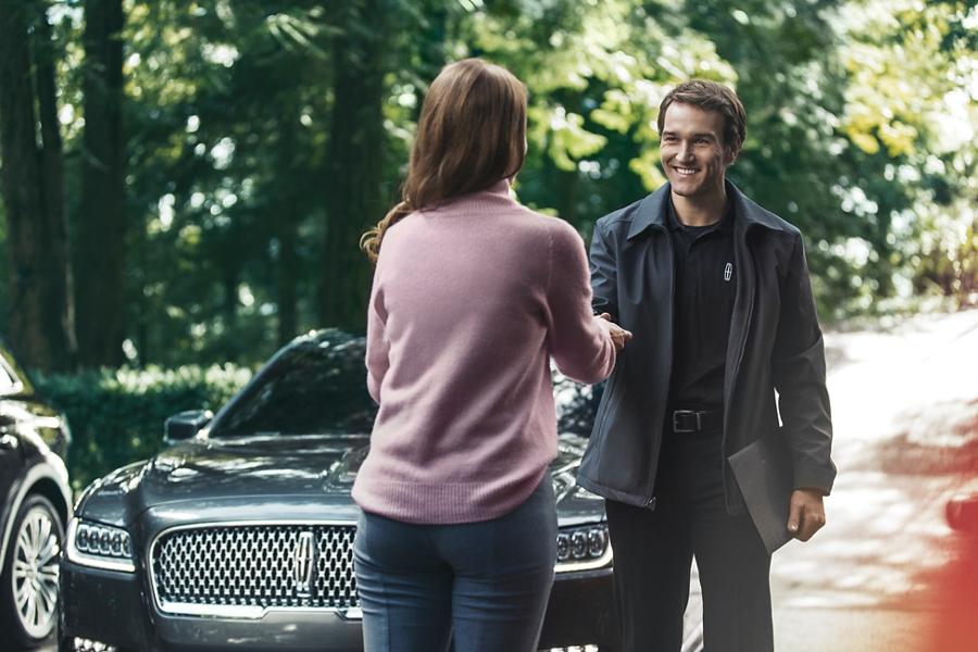 Se muestra un representante de Lincoln entregando un juego de llaves a un cliente después de realizar el servicio de recogida y entrega
