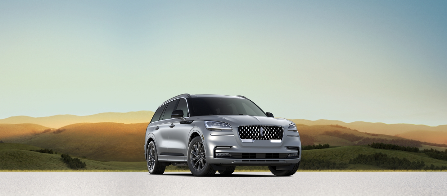 A Lincoln Aviator Grand Touring model is shown heroically positioned with rolling sun kissed hills in the background