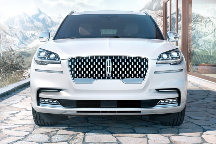 The unique front grille of the Lincoln Aviator Black Label is shown with snowy mountains in the background