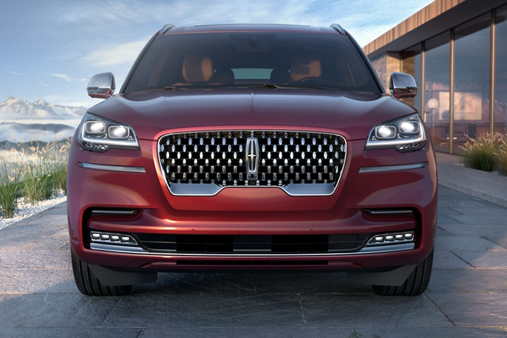 The front grille of a Lincoln Aviator Black Label is shown as the vehicle is parked in the drive of a modern retreat
