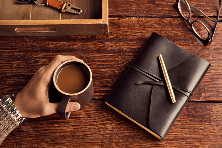 A hand is shown holding a warm cup of coffee next to a personal journal to demonstrate the inspiration of the destination theme