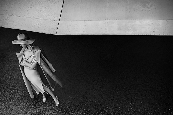 A woman is shown standing underneath the wing of a private jet