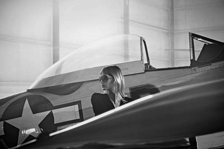 A fashionably dressed woman is shown near an airplane inside a private hangar