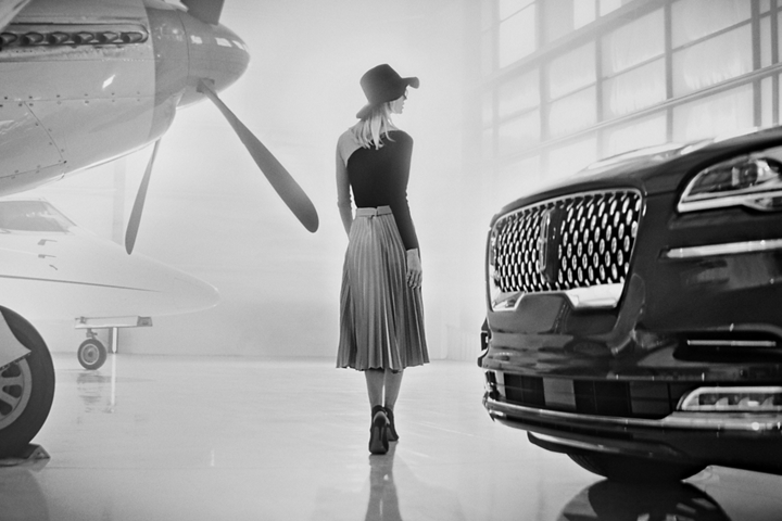 A woman is shown walking in a hangar between a propeller powered airplane and a Lincoln Aviator Black Label