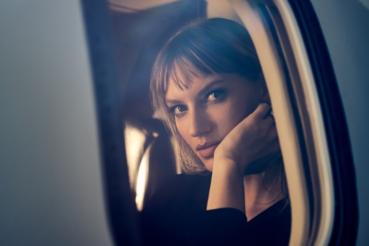 A woman is shown as she peers through the window of a private jet