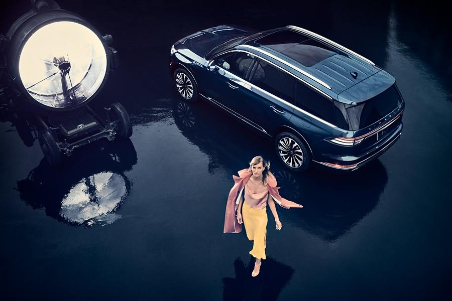 Imagen de una mujer alejándose de una Lincoln Aviator Black Label mientras que un faro ilumina hacia arriba