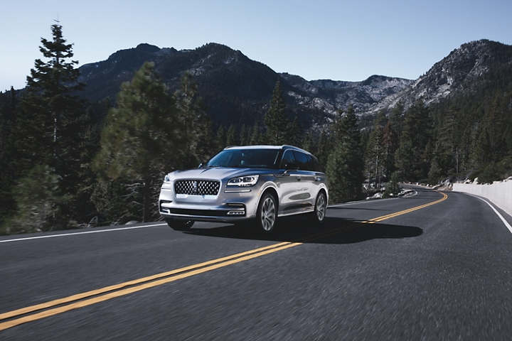 A Lincoln Aviator Grand Touring hybrid model is shown being driven on a tree lined road